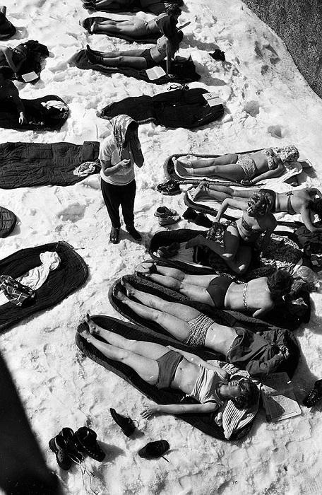 Женщины принимают солнечные ванны несмотря на лежащий вокруг снег.