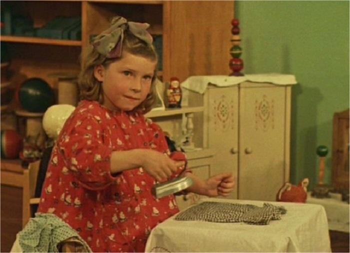 Девочка гладит одежду своей кукле.