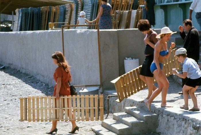 Деревянные шезлонги помогали многочисленным отдыхающим поудобнее устроиться на галечном пляже.
