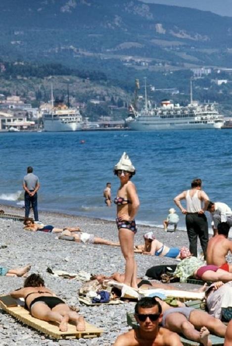 Перед отдыхающими на пляже открывается замечательный вид на город и далекие горы.