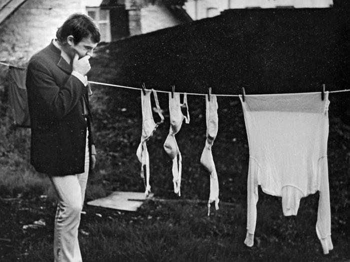 Мужчина в задумчивой позе возле сушилки с бельем.