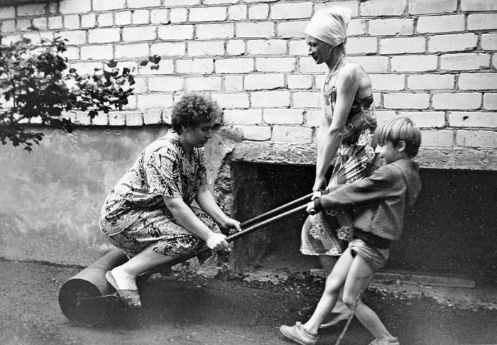 Женщины и ребенок катают асфальт катком возле дома.
