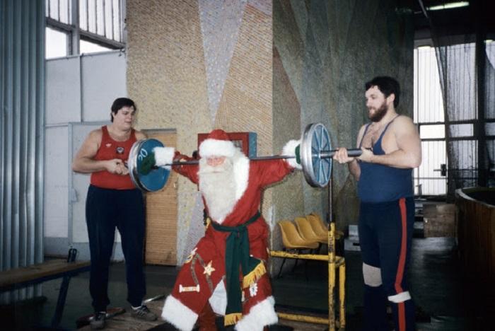Дед Мороз пытается поднять спортивный снаряд, под чутким руководством спортсменов.
