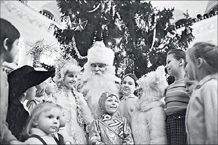 Новогодний персонаж в окружении счастливых детей, которые верят в сказку, волшебство, деда Мороза и Снегурочку.