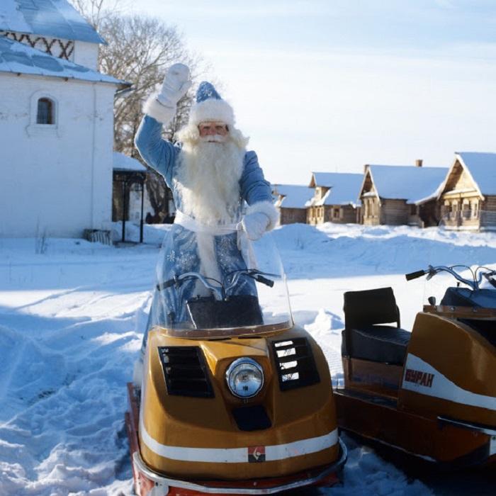 Дед Мороз в голубой шубе приветственно машет рукой, садясь на снегоход «Буран».