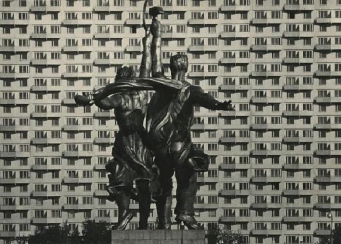Рабочий и колхозница с поднятыми над головами серпом и молотом.