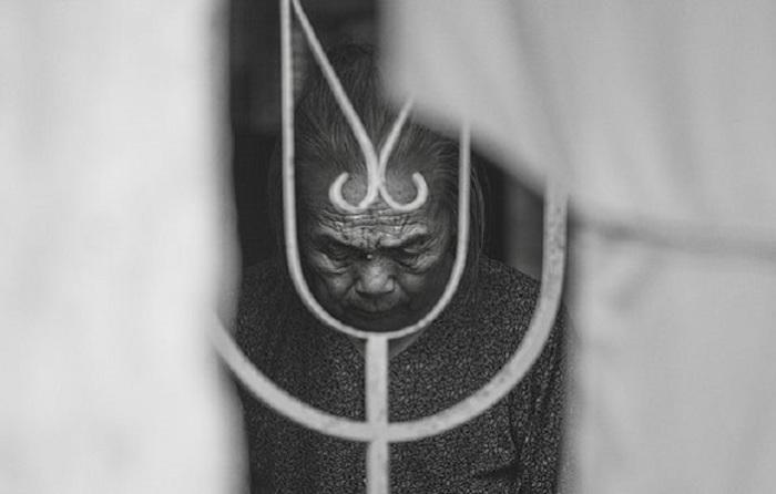 Линии на лице человека в возрасте, за железным ограждением, представляют жизненные истории и традиции, которые удалось передать фотографу.