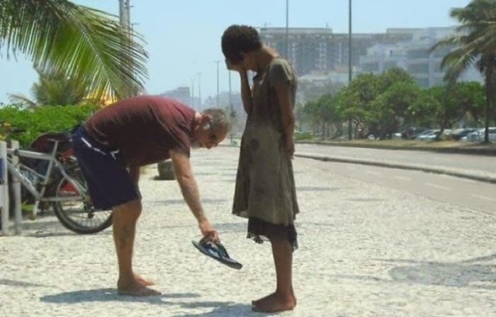 Человек, дающий свою обувь бездомной девочке в Рио-Де-Жанейро.