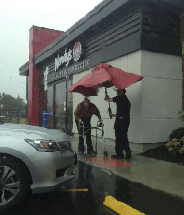 Сотрудники магазина вынесли зонтик со стола на улицу, чтобы помочь пожилому мужчине пройти под дождем к машине.