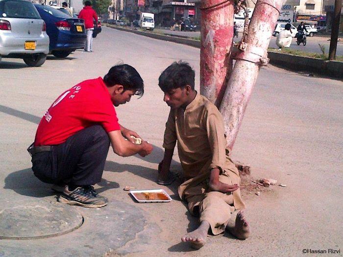 Официант покупает еду и кормит инвалида в Карачи, Пакистан.