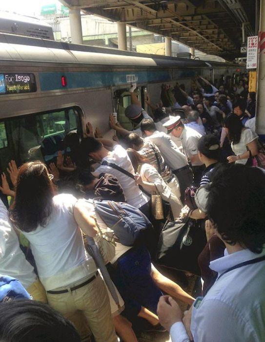 Люди вместе поднимают поезд, чтобы спасти человека, застрявшего между вагоном и платформой.