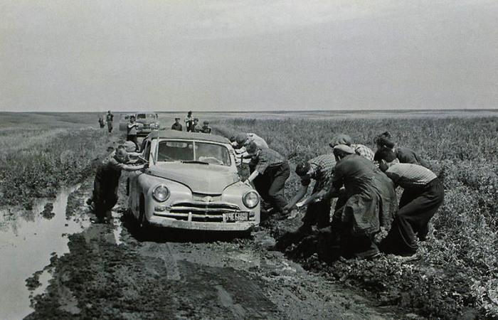 Люди, которые помогают вытолкать из грязи учебный автомобиль.
