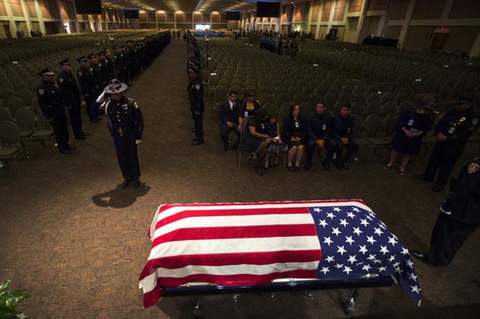 Офицер отдает честь членам семьи погибшего офицера Хосе Гилберта Веги.