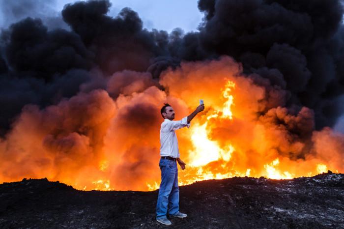 Мужчина делает фотографию напротив пожара от нефти.