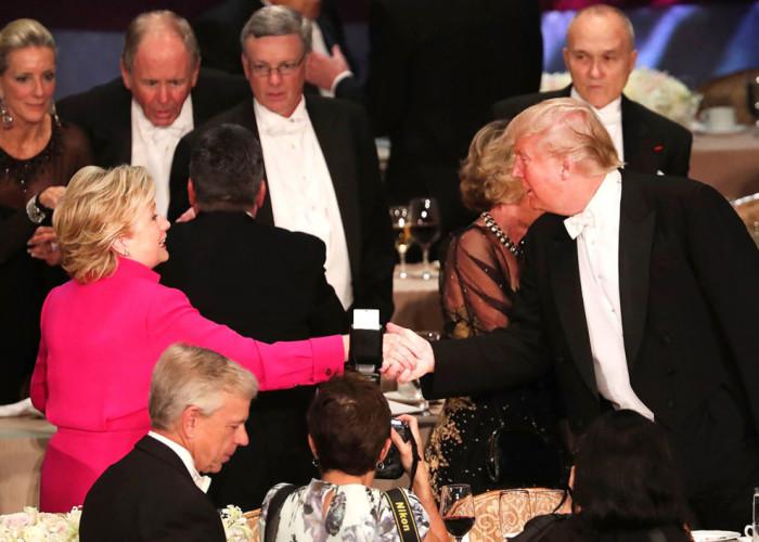 Хиллари Клинтон пожимает руку Дональду Трампу во время благотворительного ужина.