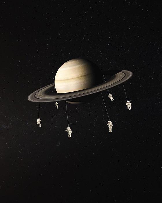 Космонавты в скафандрах катаются на кольцах Сатурна.