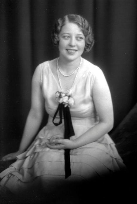 Портрет улыбающейся девушки в вечернем платье с оборками и жемчужными бусами.