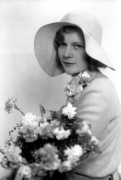Неизвестная девушка в нарядном платье, декорированном объемным цветком.