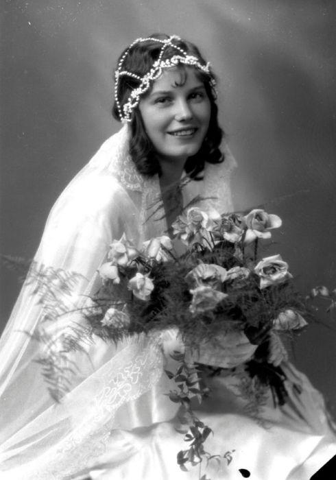 Счастливая невеста в белоснежном платье в студии фотографа.