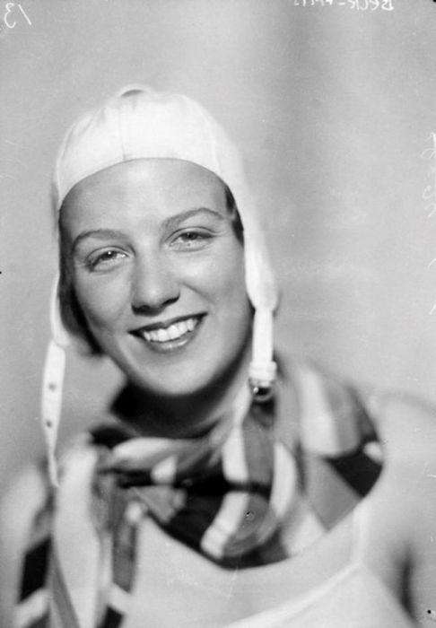 Черно-белый портрет улыбающейся женщины-спортсменки.