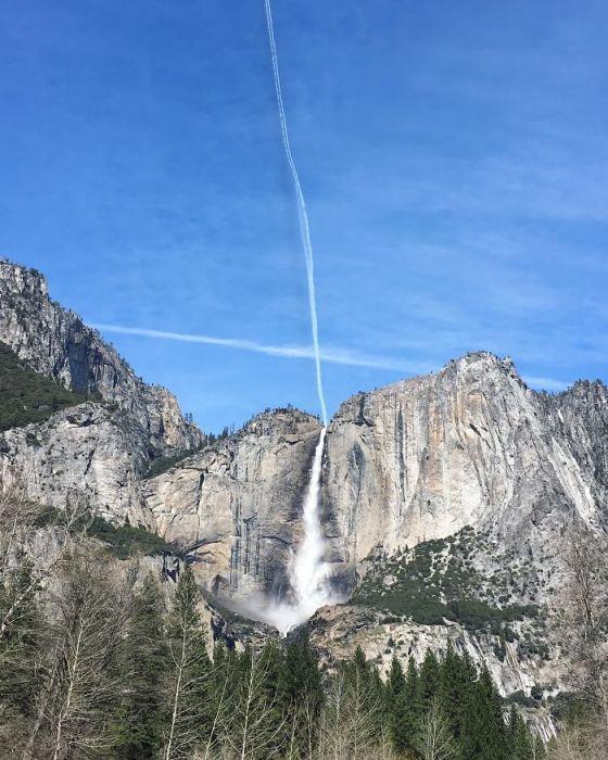 След от самолета выглядит как низвергающаяся с неба вода, которая превращается в водопад.