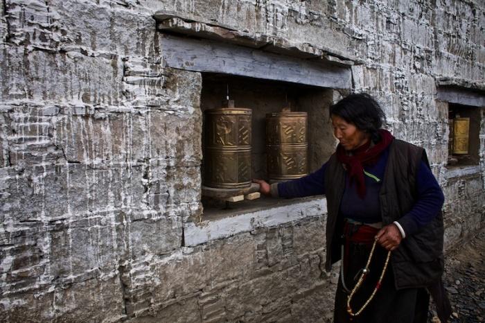 Старая тибетская женщина поворачивает цилиндры, которые сделаны из позолоченной бронзы и покрыты буддийскими надписями и символами, произнос я мантру Ом Мани Падме Хум.