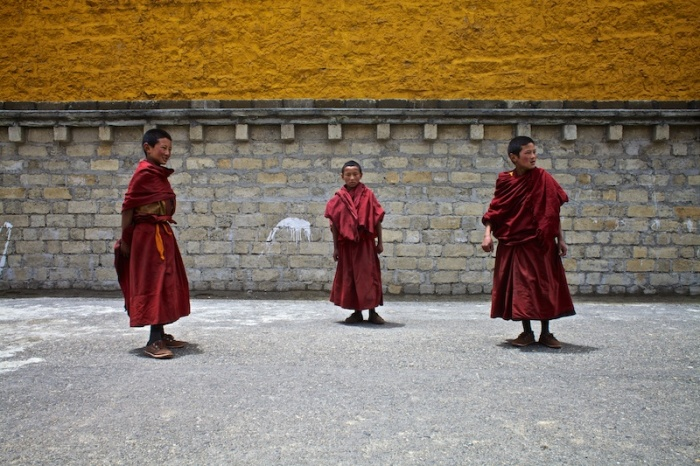 Мальчики, играющие возле храма Ганден Тубчен Чоххорлинг, внимательно слушают учителя, который вышел вернуть их в монастырь.