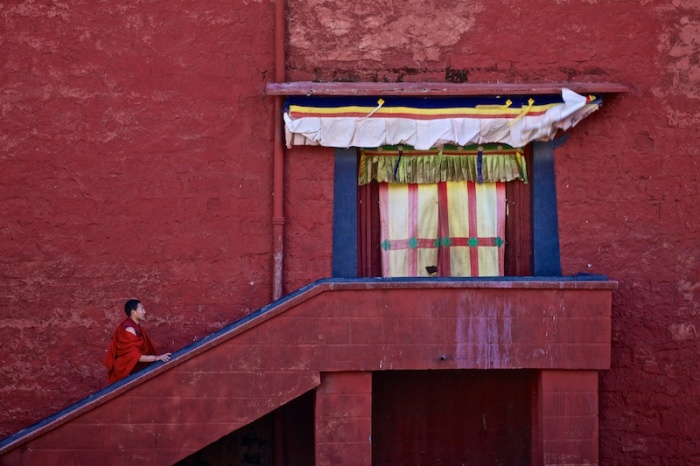 Монах направляется к черному входу храма с красочными стенами, основанного третьим Далай-ламой Сонамом Гьяцо в 1580 году, для проведения молитвы.