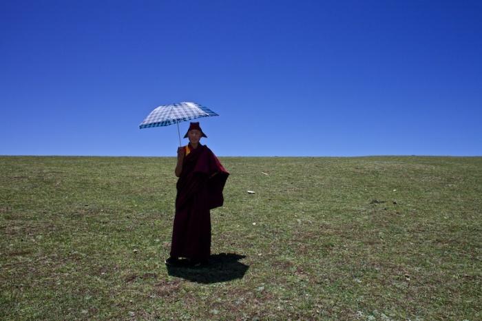 Этот регион славится чрезвычайно изменчивой погодой, поэтому монах предусмотрительно взял с собой зонт, чтобы укрыться от солнца и защититься от дождя.