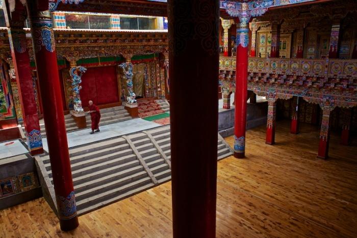 Монах в красочном расписном интерьере монастыря, что расположен небольшом городке Литанг на высоте 4014 метров над уровнем моря.