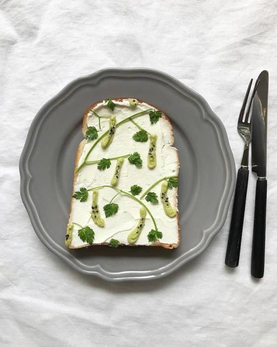 Для создания этого необычного летнего овощного тоста использовались веточки петрушки, кунжут и дынный перец.