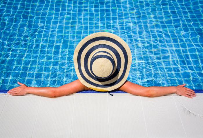Женщина в соломенной шляпке релаксирует в бассейне.