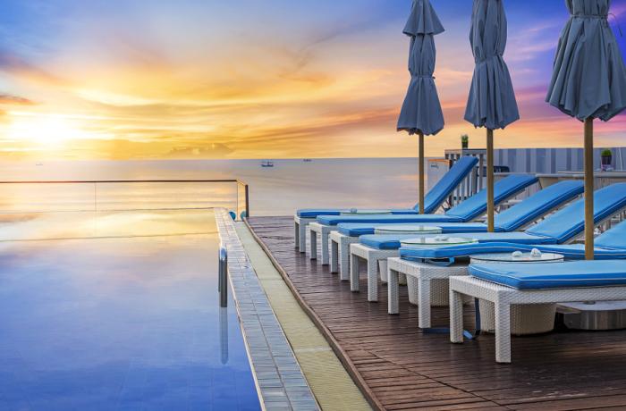 Восходящее солнце отражается в воде бассейна.