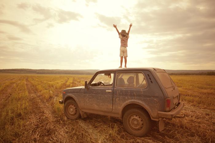 Мальчик радуется восходу солнца стоя на крыше автомобиля.