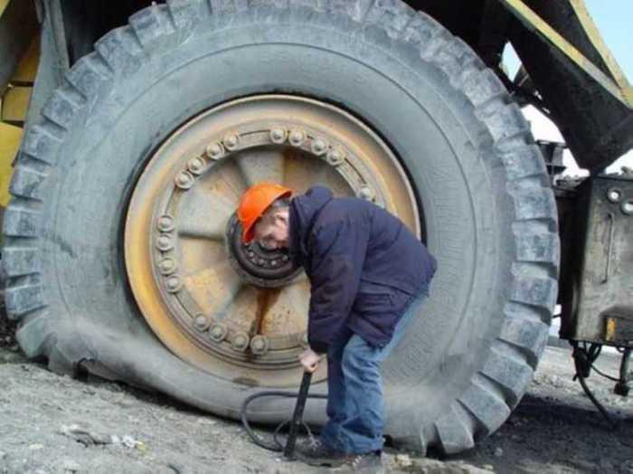 Водитель  карьерного самосвала накачивает колесо вручную...