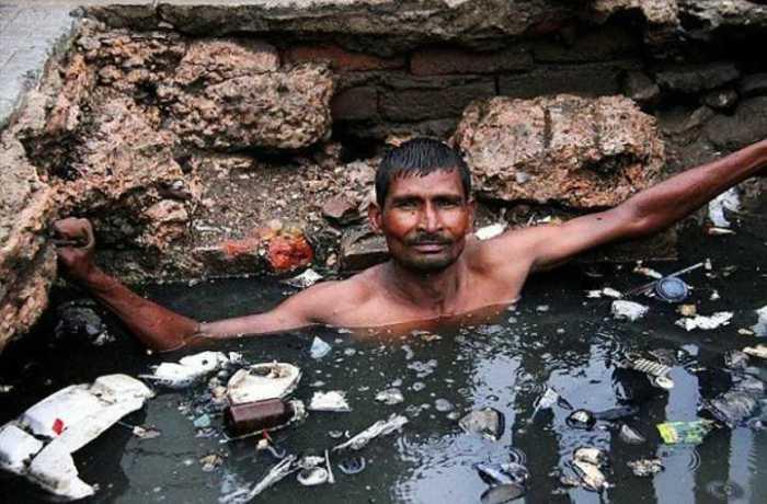 Индус проводит ремонт и чистку канализации.