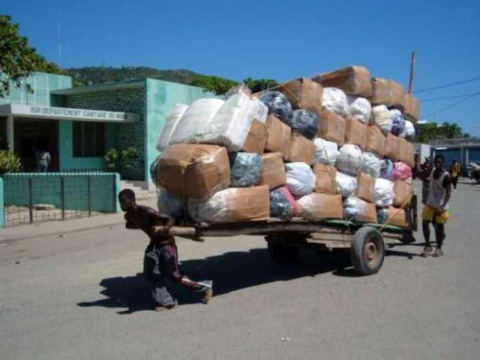 Мужчина на двухколесной повозке перевозит огромное количество баулов.