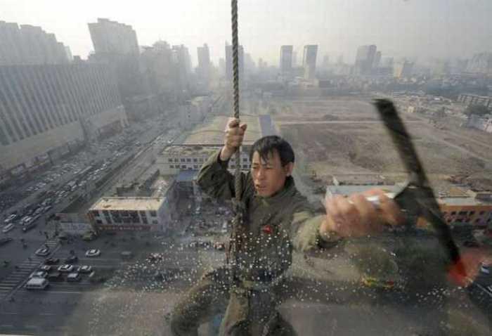 Мойщик стекол очищает внешнюю сторону небоскреба одной рукой, а другой - держится за трос-страховку.