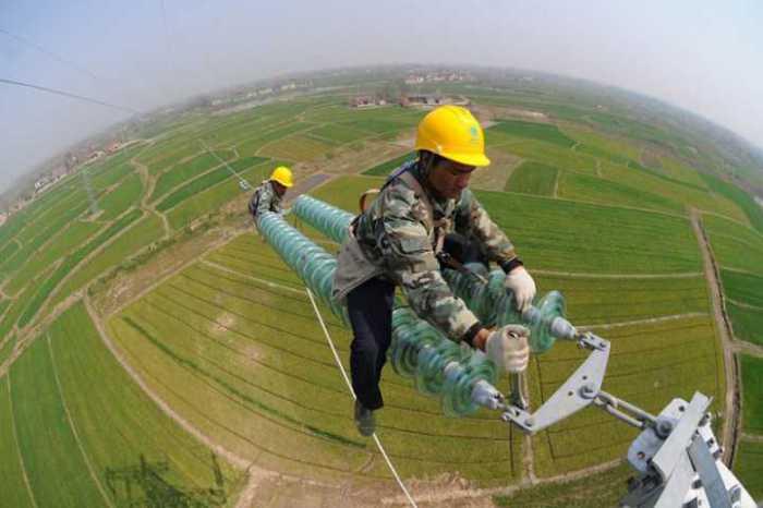 Ловкость и не боязнь высоты - главное в работе высоковольтников Китая.