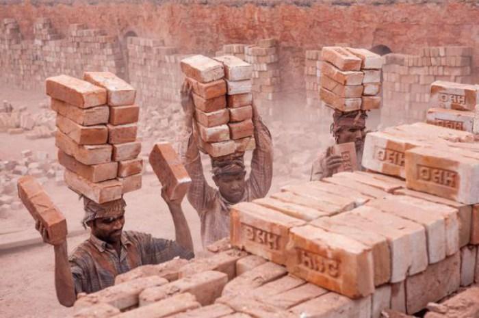 Рабочие переносят кирпичи на своих головах.