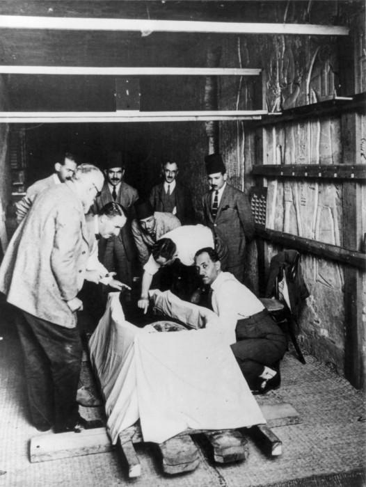 Говард Картер впервые рассматривает мумию фараона.
