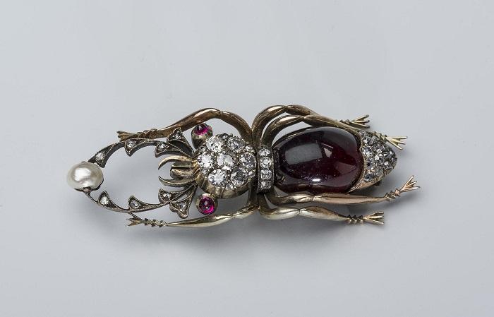 Брошь производства мастерской Н. Ф. Кемпера, украшенная камнями – рубинами, бриллиантами и жемчугом.