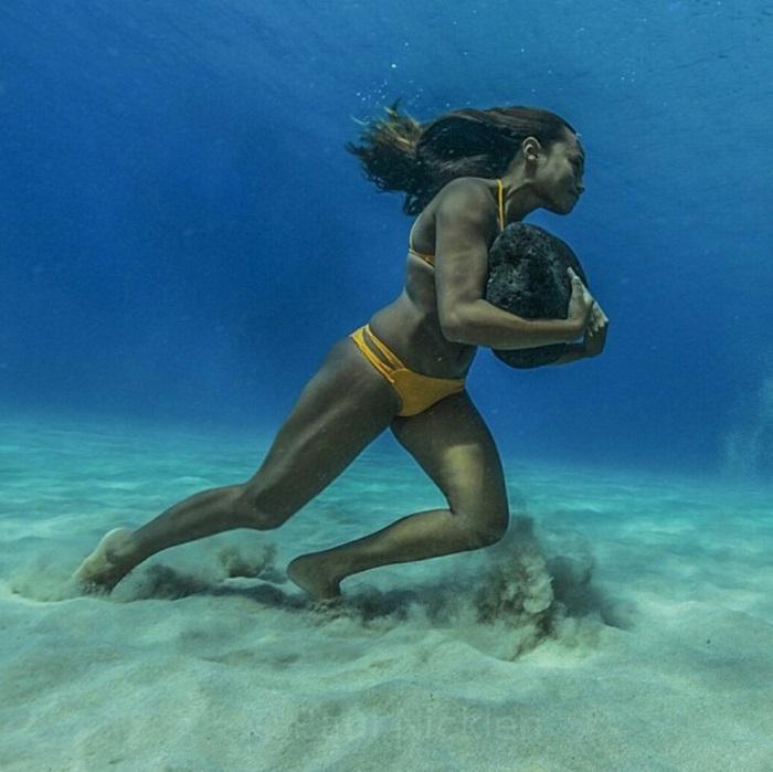 Девушка бегает по дну океана с 20-килограммовым камнем, чтобы иметь силы противостоять ударам волн.