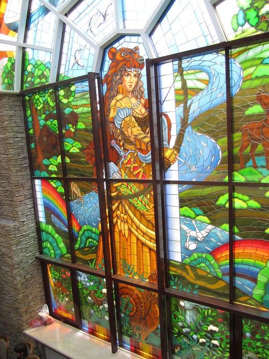 Яркий, красочный витраж изображает, прицеливающуюся из охотничьего лука, стройную амазонку.