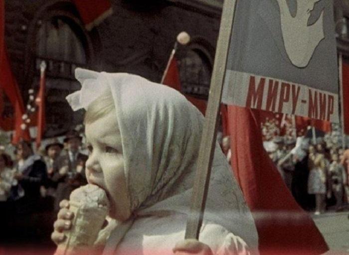 Девочка кушает мороженное на параде, который посвящён дню международной солидарности трудящихся.