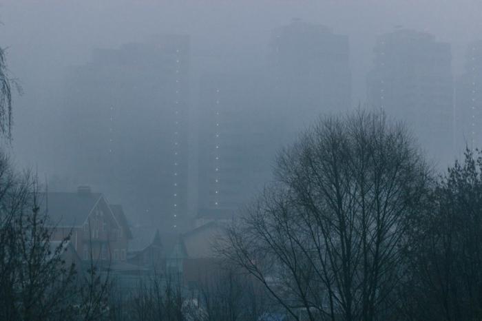 Вечерний город в голубой туманной дымке.
