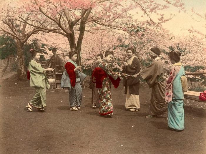 Девушки играют в жмурки в парке Ногэяма под цветущими сакурами, Йокогама. Автор фотографии: Кусакабэ Кимбэй, 1880—1890-е года.