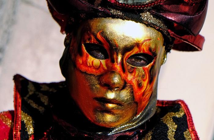 Участник карнавала в огненной маске.