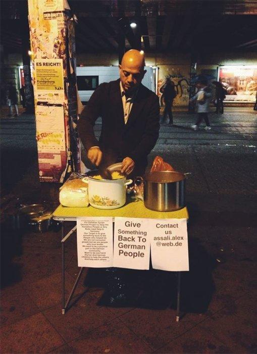 Беженец из Сирии раздает малоимущим еду в одном из городов Германии.