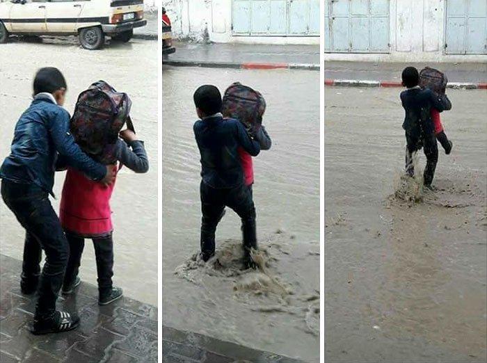 Старший брат переносит на руках через лужу свою младшую сестру.